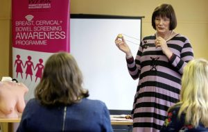 Anne McGale, facilitator from the Women's Resource and Development Agency, demonstrates how to look for abnormal breast lumps Picture by Mal McCann Irish News